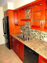 The kitchen is remodeled with custom design African Mahogany Cabinets, glass tile back splash and warm tones in the granite counter