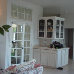 BEFORE the REMODEL: The main living space was divided by the wet bar and a screened in lanai that closed off the space with the glass french doors.