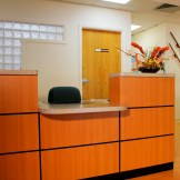 Lobby reception desk. Desk is custom designed in maple with black recessed reveals.