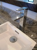 Square vessel sink and Moen 90 Degree faucet keep the linear crisp lines of the design scheme.
