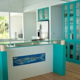 View of kitchen from dining room. Custom floating glass counter with custom tile inset below creates bar height counter.